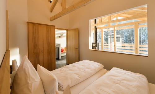 Im Schlafzimmer des Forstgut Chalets genießen Sie den Blick in die Natur des Bayerischen Waldes