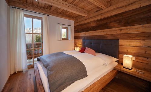 Traditioneller Almhüttencharme in den Schlafzimmer der Chalets Almidylle Piredt