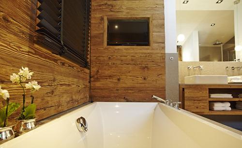 Design Chalet im Allgäu- Badezimmer mit Badewanne und Flachbild TV